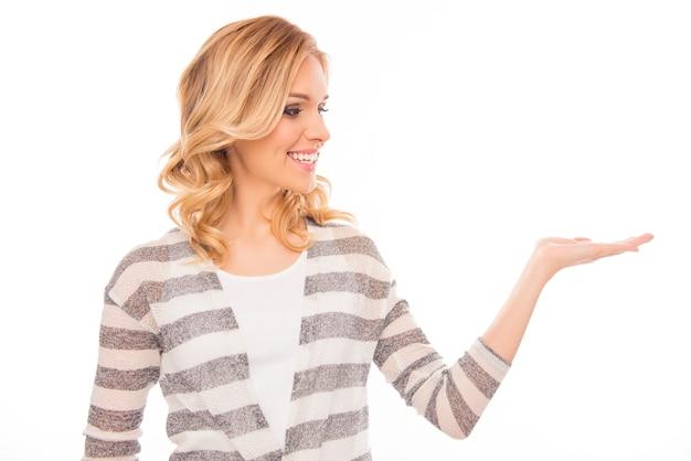Портрет счастливой улыбающейся блондинки, представляющей продукт