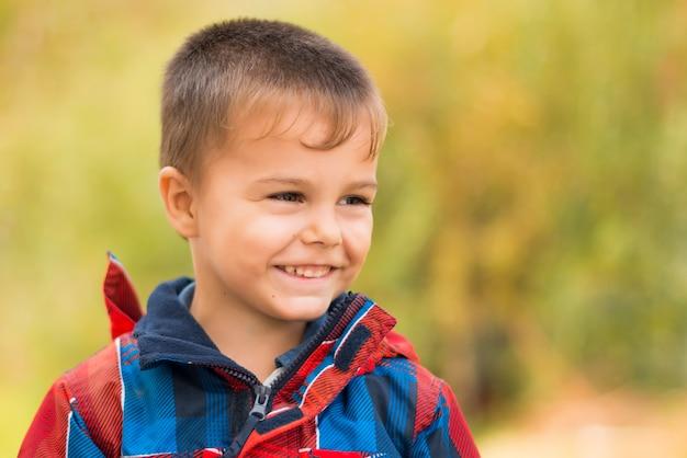 公園で幸せな笑みを浮かべて男の子の肖像画。