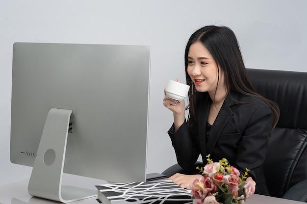 커피 컵을 들고 노트북 컴퓨터와 함께 행복 하 게 웃는 비즈니스 아시아 여자의 초상화. 기술 및 통신 개념.