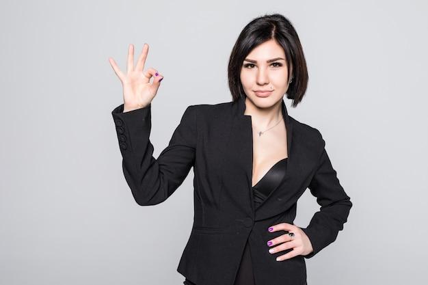 Портрет счастливой улыбающейся деловой женщины с нормальным жестом, изолированной на белом