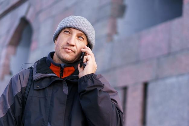 벽돌 벽 배경에 도시 거리에 스마트폰으로 행복 웃는 백인 남자의 초상화...