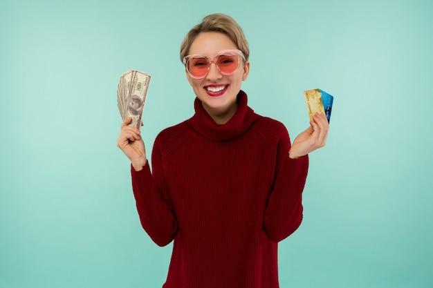 Портрет счастливой улыбающейся кавказской женщины, держащей деньги кредитной карты и долларов сша, глядя на камеру, изолированную на синем фоне.