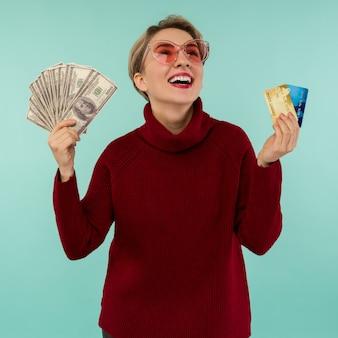 파란색 배경 위에 절연 카메라를 보면서 신용 카드와 미국 달러 돈을 들고 행복 하 게 웃는 백인 여자의 초상화.