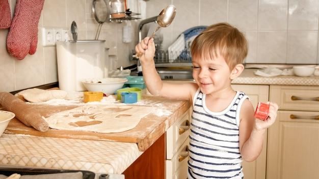 행복 미소 명랑 소년 요리와 집에서 부엌에서 베이킹의 초상화