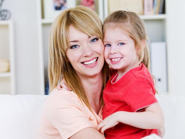 Портрет счастливой улыбающейся веселой матери с дочерью в обнимку - в помещении