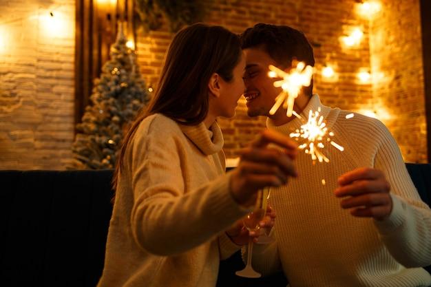 Портрет счастливой улыбающейся пары с бокалами шампанского, держащими бенгальские огни