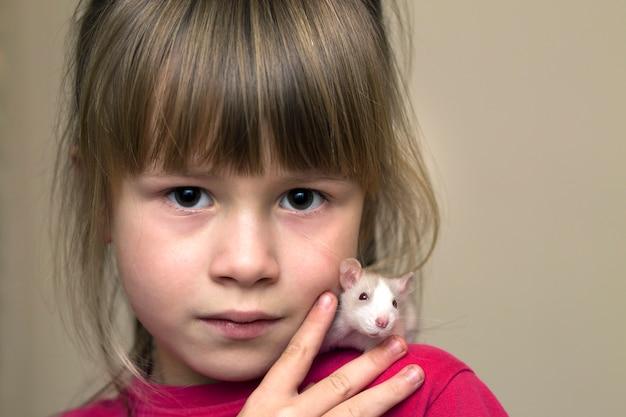 Портрет счастливой усмехаясь милой девушки ребенка с белым хомяком мыши любимчика на светлом космосе экземпляра. держать домашних животных в домашних условиях, уход и любовь к животным концепции.