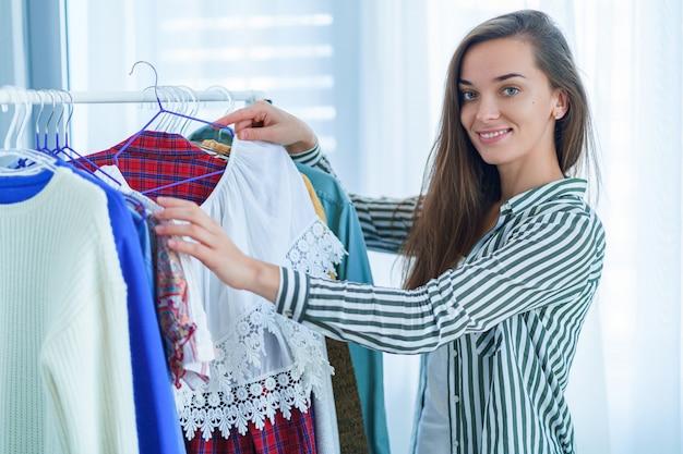 ショッピングや布のブティックで着用する服を選択中にモダンなトレンディなファッショナブルなスタイリッシュな女性服のワードローブラックの近くに立って幸せな笑顔かわいい若いブルネットの女性の肖像画