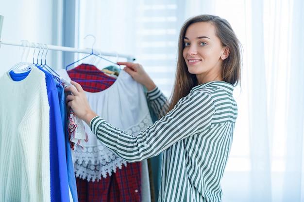 幸せな笑顔のかわいい若いブルネットの女性のショッピングの間にワードローブラックの近くに立って、流行のファッショナブルなスタイリッシュな女性の服の買い物や服を着る服を選ぶ布の店での肖像画