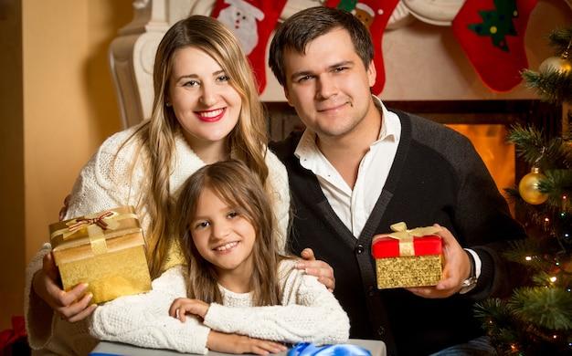 크리스마스에 벽난로에서 포즈를 취하는 행복한 웃는 가족의 초상화