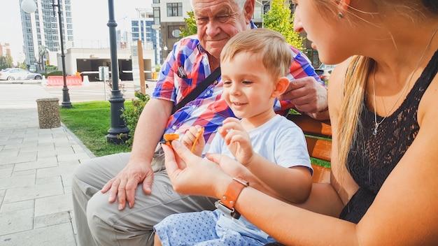 작은 유아 소년, 젊은 메이와 할아버지가 공원 벤치에 앉아 작은 플라스틱 장난감을 가지고 노는 행복 웃는 가족의 초상화