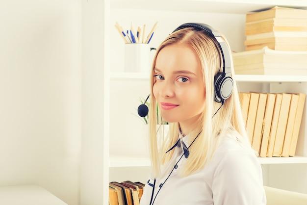 Портрет счастливого улыбающегося женского оператора телефона службы поддержки клиентов на рабочем месте.