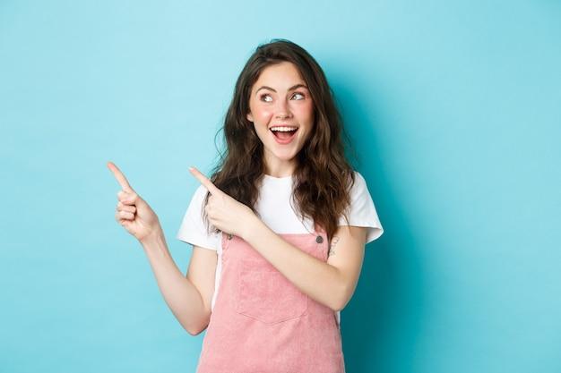 グラマー赤面、左指を指して、プロモーションオファーを見て、広告コピースペース、青い背景を示す幸せな笑顔の女性モデルの肖像画