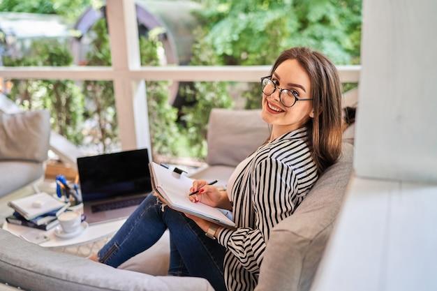 ソファにノートを持って自宅で幸せな笑顔のフリーランサーの女性の肖像画。