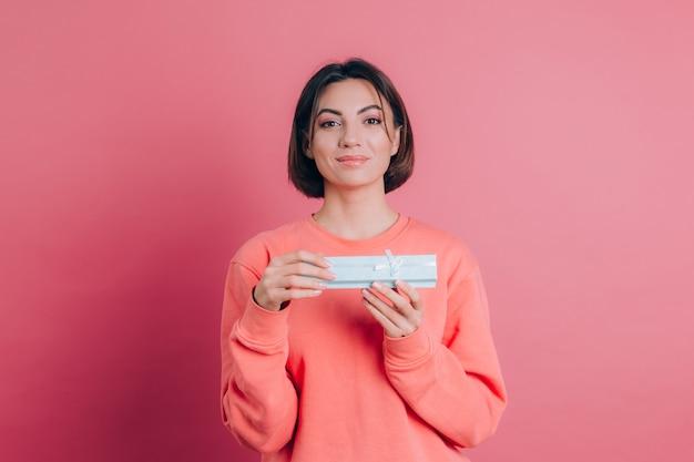 분홍색 배경에 고립 된 선물 상자를 여는 행복 웃는 소녀의 초상화