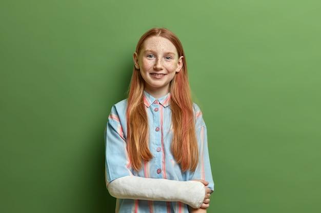 Портрет счастливой улыбающейся девушки с длинными рыжими волосами, находящейся в хорошем настроении, рада поговорить с друзьями, сломавшей руку после опасного праздника, носит полосатую рубашку, позирует у зеленой стены.