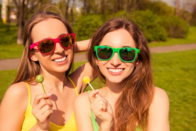 Портрет счастливых улыбающихся девушек в очках с леденцами на палочке