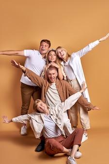 Портрет счастливой улыбающейся группы молодых людей, позирующих вместе, в модных пальто, рубашках