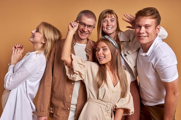 Портрет счастливой улыбающейся группы молодых людей, позирующих вместе
