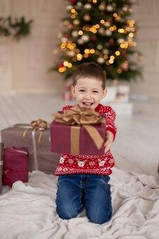 クリスマスプレゼントボックスと赤いニットセーターで幸せな笑顔の小さな男の子の肖像画