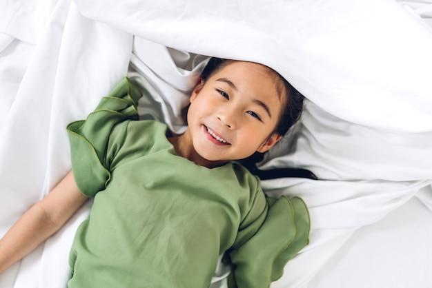 白いベッドに横たわって楽しんで幸せな笑みを浮かべて小さな子供アジアの女の子の肖像画、