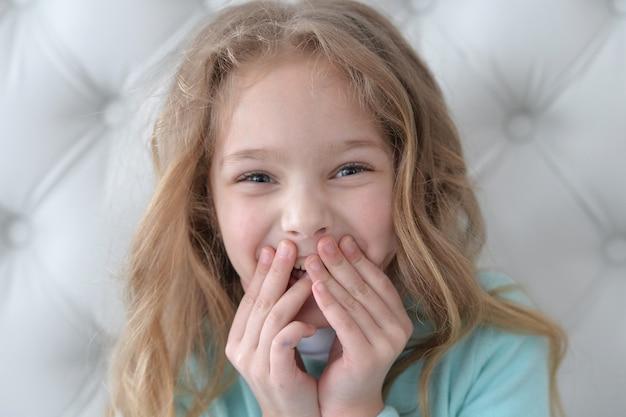 顔に手を持って幸せな笑顔の少女の肖像画
