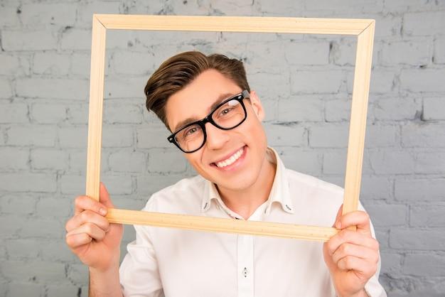 木製のフレームを保持しているメガネで幸せな笑顔の男の肖像画