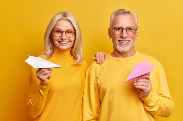 행복한 미소 중간 나이 든 여자와 남자의 초상화는 서로 옆에 서서 좋은 미래를 믿고 종이로 만든 비행기는 좋은 비전을 위해 안경을 착용하고 노란색에 고립 된 긍정적 인 감정을 표현합니다.