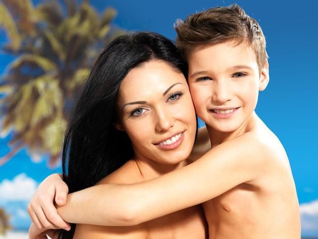 Портрет счастливой улыбающейся матери обнимает сына 8 лет на тропическом пляже
