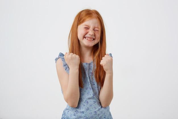 Портрет счастливой улыбающейся маленькой рыжеволосой девушки с веснушками, нижнее белье в голубом, стоит на белом фоне с кулаками вверх.