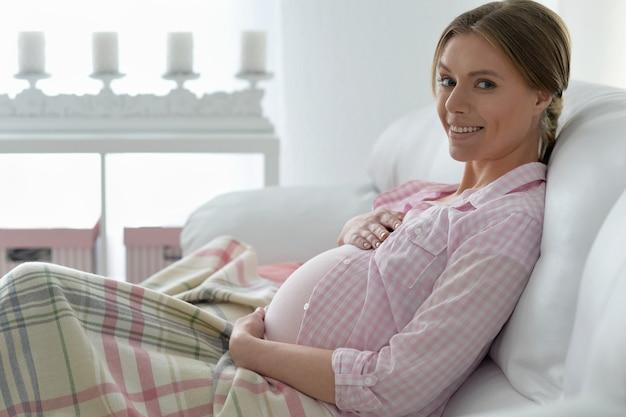 ベッドで幸せな笑顔の妊婦の肖像画