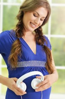 ヘッドフォンで幸せな笑顔の妊婦の肖像画