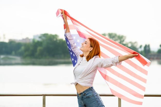 彼女の手に米国国旗を持つ幸せな笑顔の赤い髪の少女の肖像画。アメリカ合衆国の独立記念日を祝うかなり若い女性。国際民主主義デーのコンセプト。