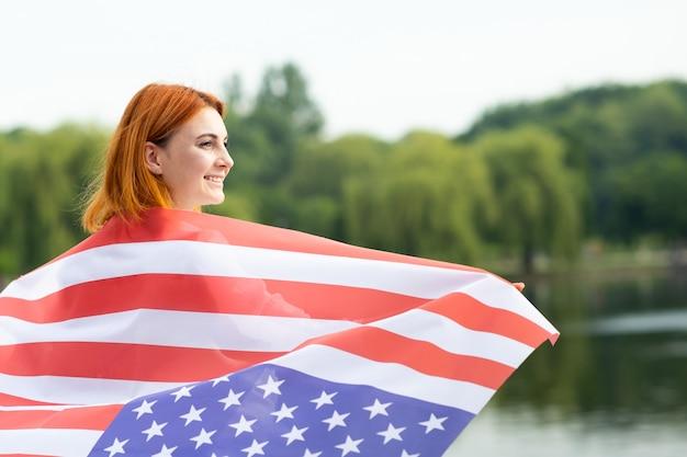 Портрет счастливой улыбающейся рыжеволосой девушки с национальным флагом сша на ее плечах. положительная молодая женщина празднует день независимости соединенных штатов.