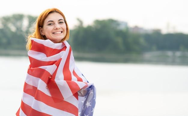 彼女の肩に米国国旗を持つ幸せな笑顔の赤い髪の少女の肖像画。アメリカ合衆国の独立記念日を祝うポジティブな若い女性。