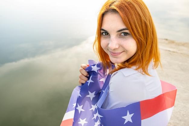 彼女の肩に米国国旗を持つ幸せな笑顔の赤い髪の少女の肖像画