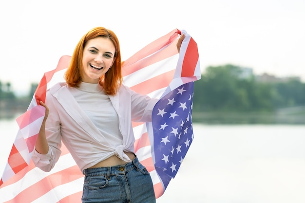 Портрет счастливой улыбающейся рыжеволосой девушки с национальным флагом сша на плечах.
