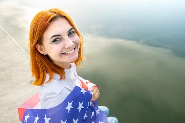 彼女の肩に米国国旗を持つ幸せな笑顔の赤い髪の少女の肖像画。
