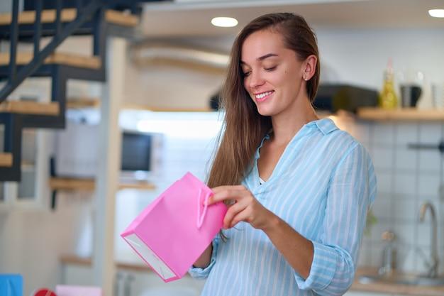 Портрет счастливой улыбающейся довольной милой любимой женщины с цветными подарочными пакетами