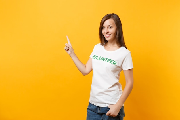 黄色の背景に分離された碑文の緑のタイトルボランティアと書かれた白いtシャツで幸せな笑顔の満足のいく女性の肖像画。自主的な無料支援支援、チャリティーグレイスワークコンセプト。
