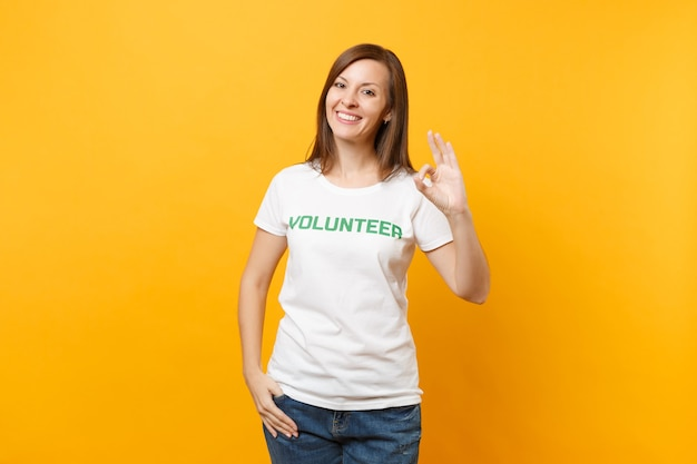 Портрет счастливой улыбающейся довольной женщины в белой футболке с написанным надписью зеленого названия волонтером, изолированным на желтом фоне. добровольная бесплатная помощь, концепция работы благотворительной благодати.