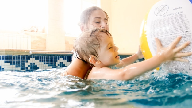 Портрет счастливого улыбающегося мальчика малыша обучения плаванию с матерью в бассейне. семья весело и отдыхает в бассейне