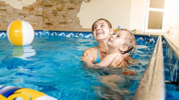 수영장에서 어머니와 함께 수영을 배우는 행복 미소 유아 소년의 초상화