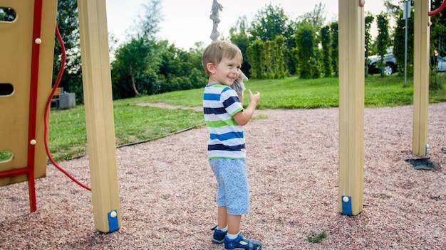 공원에서 어린이 놀이터에 등반을 위해 큰 밧줄을 가지고 노는 행복한 웃는 유아 소년의 초상화. 재미 있고 노는 활동적이고 스포티 한 어린이