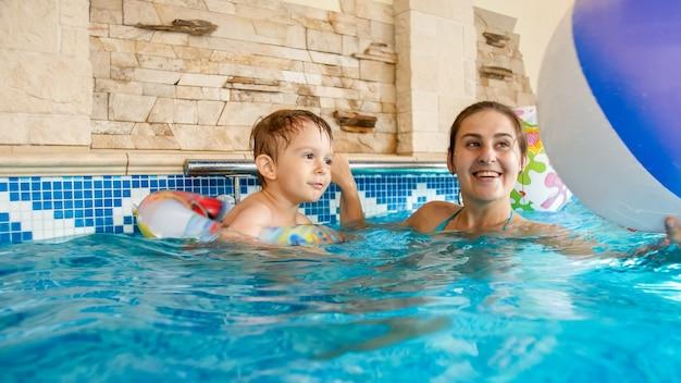 실내 수영장에서 어머니와 함께 풍선 다채로운 비치 볼을 가지고 노는 행복 미소 유아 소년의 초상화