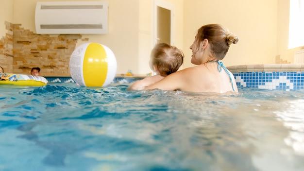 실내 수영장에서 어머니와 함께 부풀릴 수 있는 다채로운 비치볼을 가지고 노는 행복한 미소 어린 소년의 초상화 프리미엄 사진
