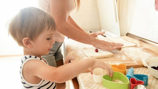 부엌에서 굽고 요리하는 젊은 어머니와 함께 웃고 있는 행복한 어린 소년의 초상화. 집에서 아이를 가르치고 교육하는 부모