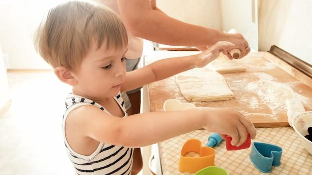 젊은 어머니 제빵과 부엌에서 요리와 함께 행복 미소 유아 소년의 초상화