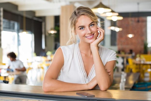 コーヒーのコーヒーカウンターで待っている幸せな笑顔の女性の肖像画