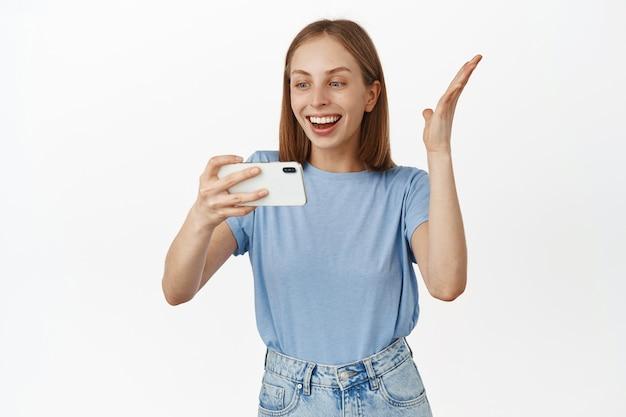 휴대폰으로 smth를 보고 기뻐하고, 스마트폰 비디오 게임에서 이기고, 밝은 화면을 보고, 흰 벽에 기대어 서 있는 행복한 웃는 여성의 초상화